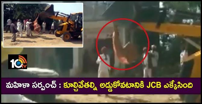 Mandawala village sarpanch rekhadevi climb a JCB machine in an attempt to stop anti-encroachment drive in Rajasthan